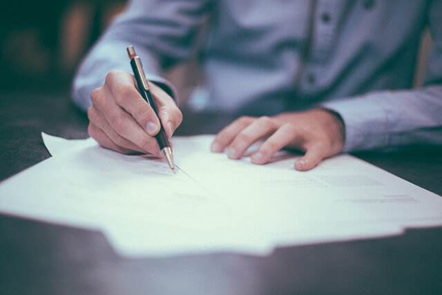 契約書にサインする男性