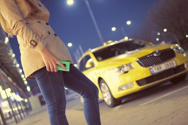 スマホをもつ女性と車