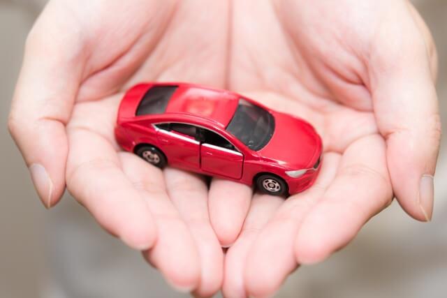 手の上に車のおもちゃがある
