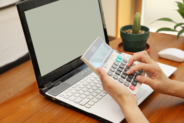 パソコンを見ながら電卓を操作