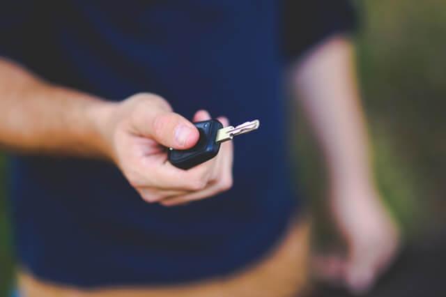 レンタカーのキーを受け取る男性