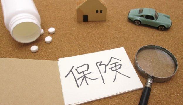 机に並べられた車と保険と書かれた紙