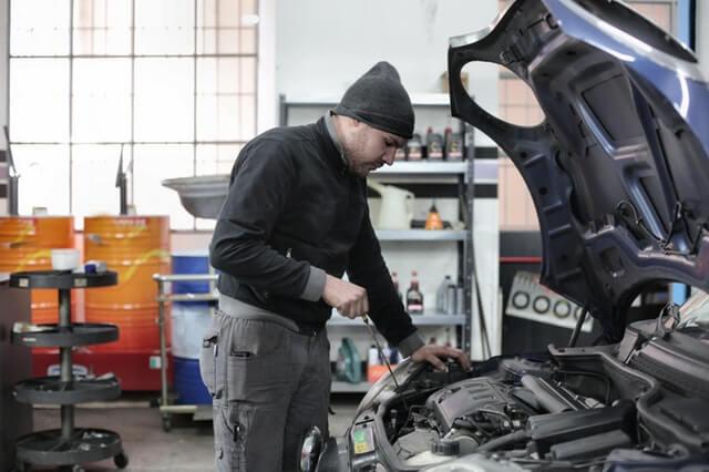 車のエンジンをチェックする作業員