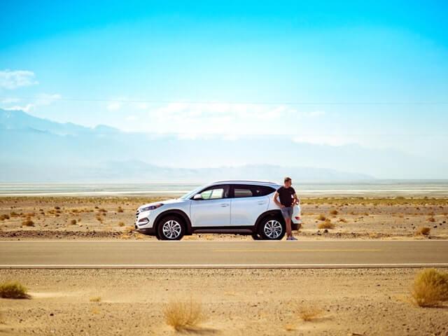 荒野にいる男性と車